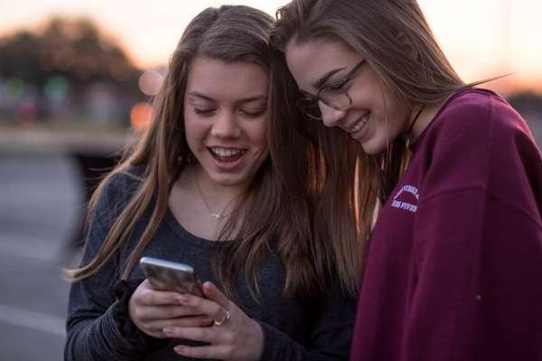 two women looking on black smartphone