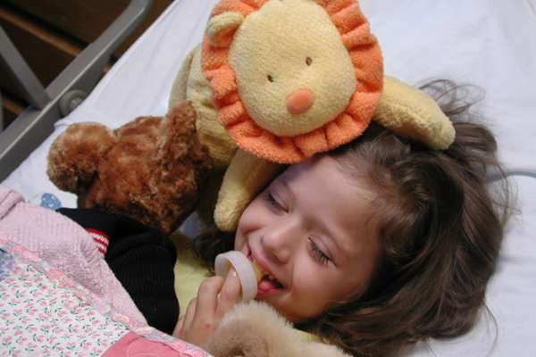 Young girls laying in hospital bed with stuffed animals smiling